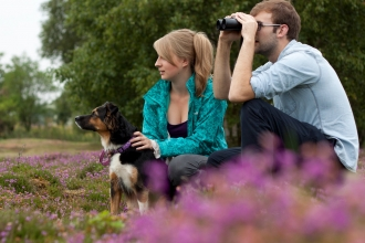 Couple birdwatching with dog
